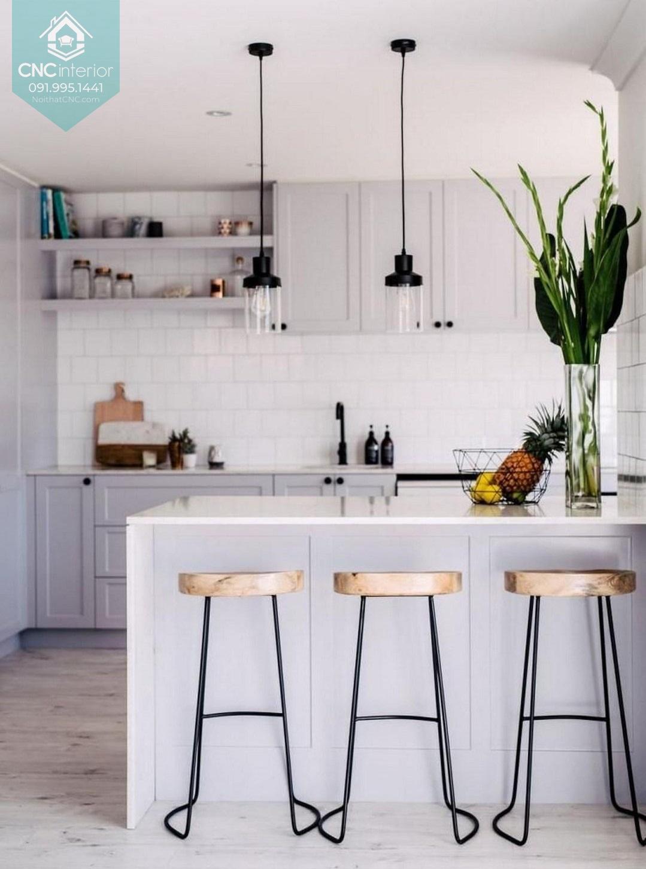 Một lọ hoa xanh nổi bật trên gian bếp màu trắng tinh tế.